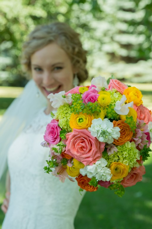 Wedding bouquet of Coral, Pink, Yellow, Chartruse and White Flowers. Roses, Stock, Mini Hydrangea, Button Poms, Ladies Mantle